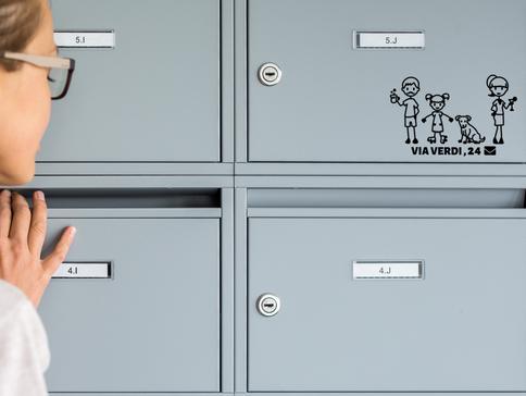 Giovane donna sveglia che ispeziona la sua cassetta postale per nuove lettere