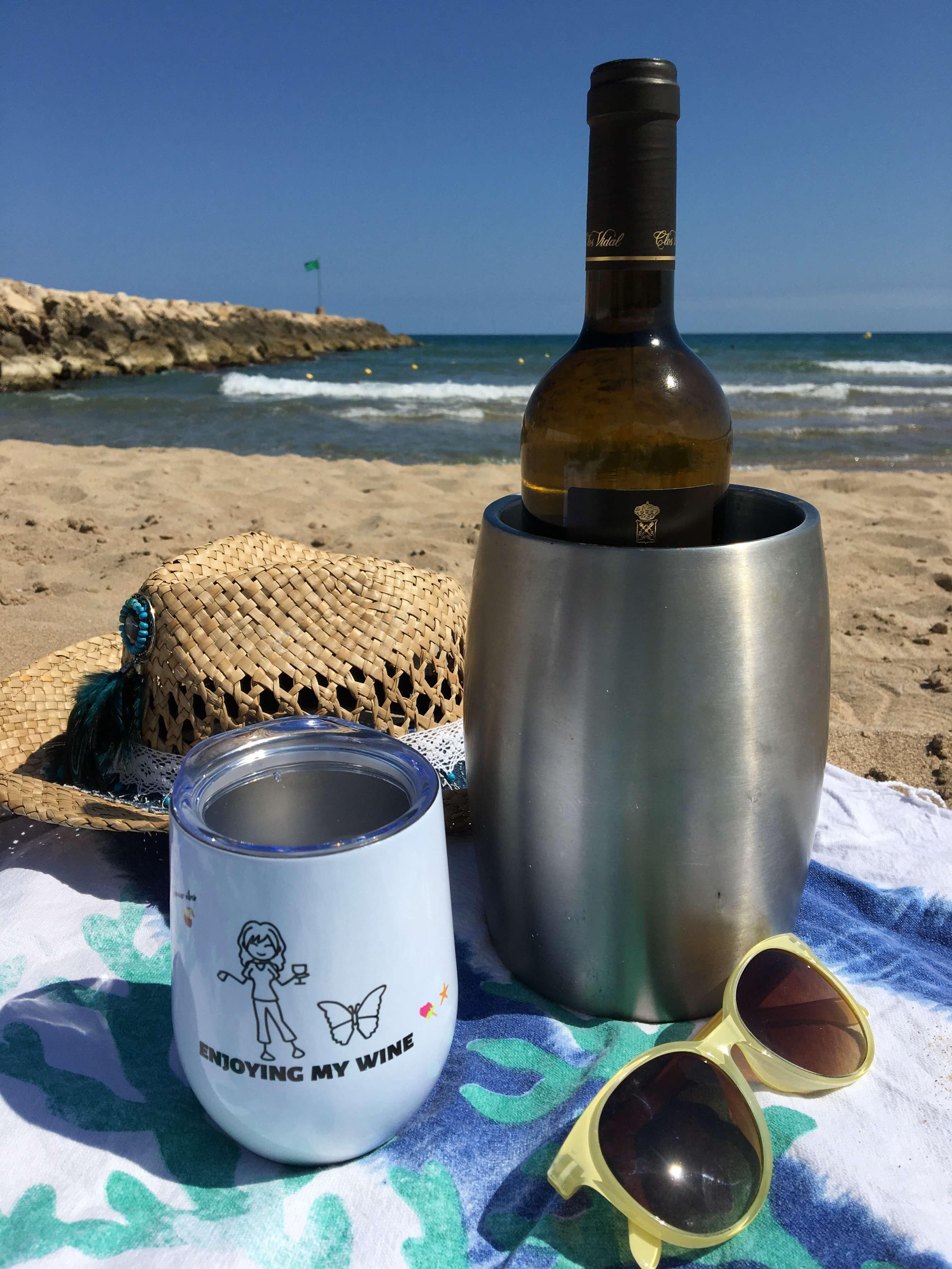 Njuter av en dag på stranden med vin och en vinbägare.